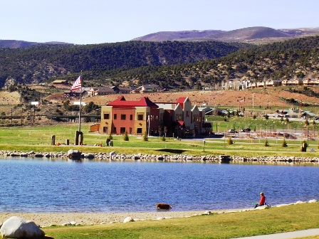 Lake in foreground with a red municipal building and mountains in the background.